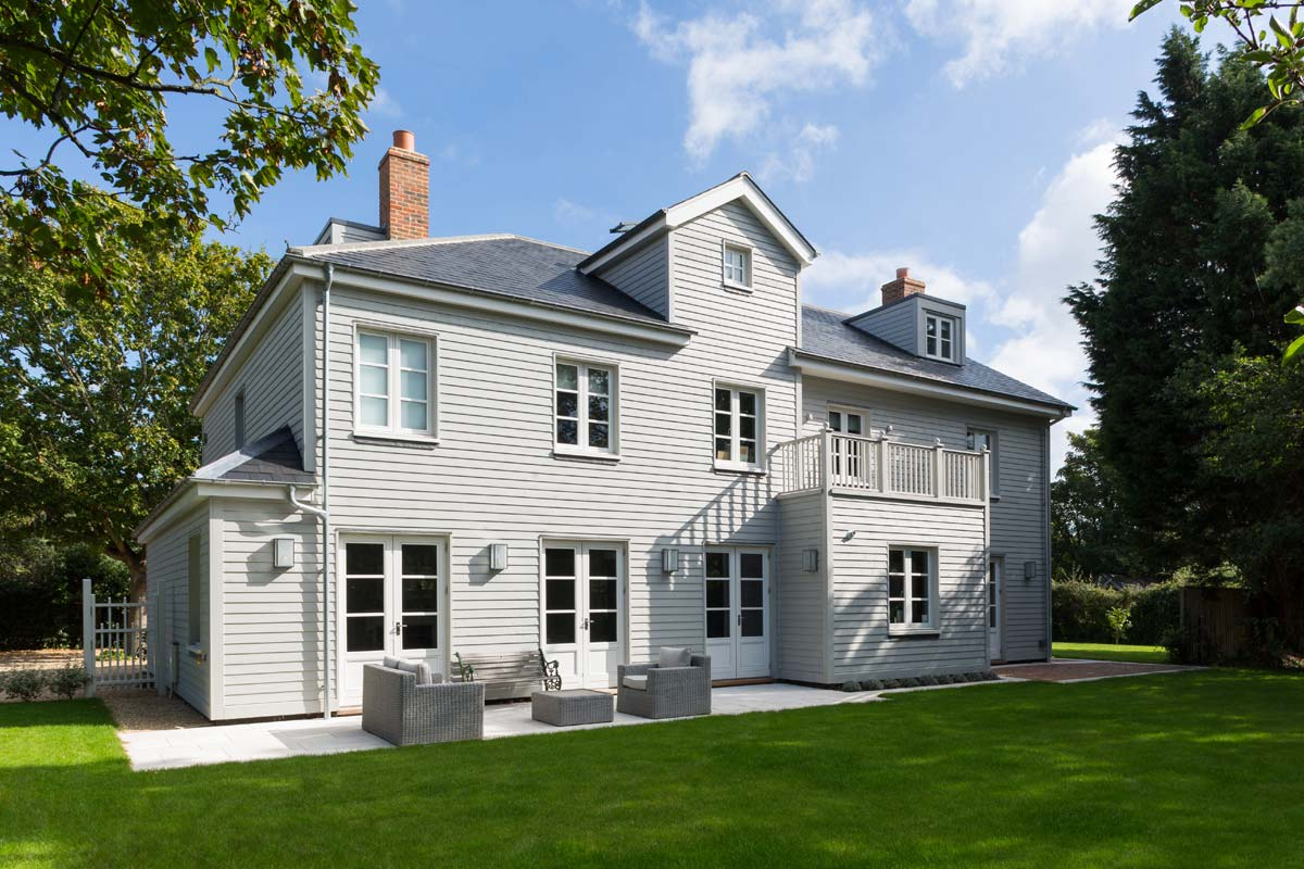 New build, New England style house with horizontal timber boarding and grey slate roof